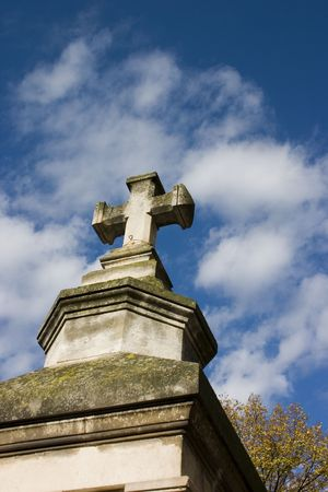Aged, molded monument wtih cross against and intense blue and white sky photo