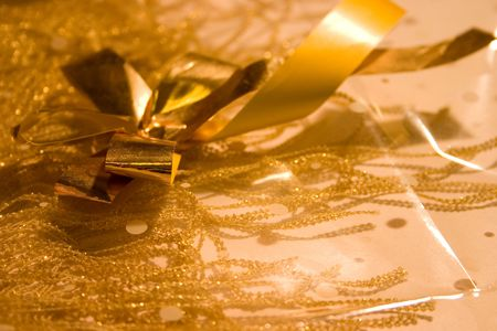 cellophane: Gold woven fringed material overlaid with cellophane and gold ribbon.