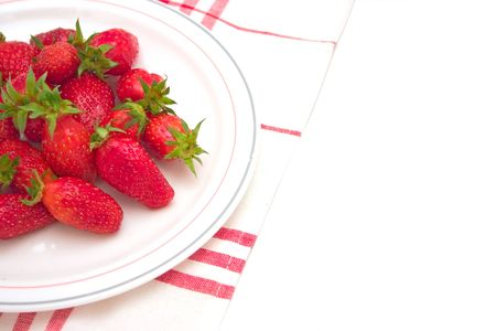 clothe: Isolated plate of strawberries on red and white clothe.