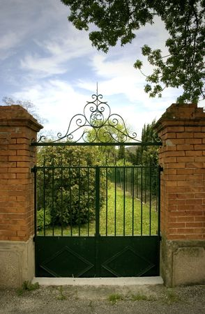 iron gate: Straight on shot of a nice brick and black wrought iron gate with view of the garden and sky.