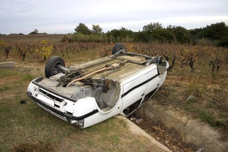Car involved in a wreck turned upside down over a culvert. It looks like it made a perfect landing. photo