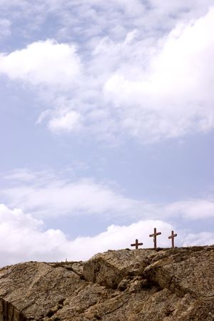 depict: Looking over a large rock in the foreground catching just enough of 3 crosses in the distance and a beautiful sky to depict a sense of faith and spirituality.