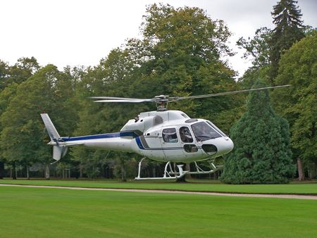 helicopter pad: A white helicopter on a field Stock Photo
