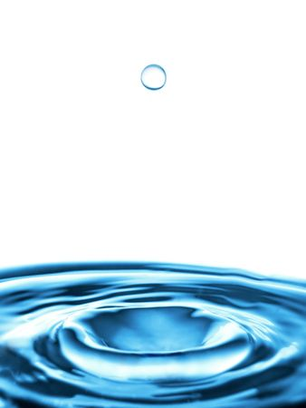 A spheric water drop falling down to the rippled water
