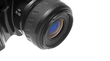 ring flash: Closeup of the lens of a black SLR camera. Viewed from the left. Space at the right of the image. Isolated over white background.