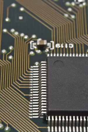 soldered: A dark microprocessor on a circuit board.