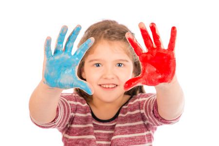 pintura en la cara: Linda niña jugando con pintura roja y azul que muestra sus manos. Centrarse en las manos.