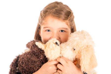 holding close: An adorable little girl holding three plush toys close to her face. Isolated on white.