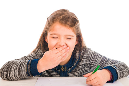 An adorable little girl sitting before a table writing on a sheet of paper and yawning photo