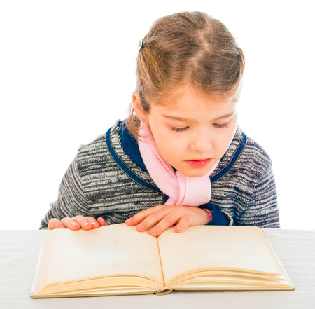 A cute little girl reading an open book on a table focusing on the text. The book is blanked-out.
