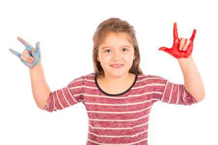 Cute little girl with painted hands showing the horns and smiling. Isolated on white. Stock Photo