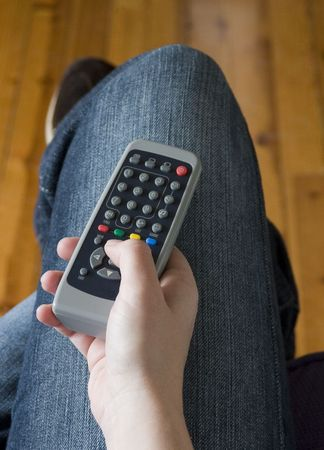 changing channels: A person with the TV remote on their knee in the process of changing channels to see what is on the other station.