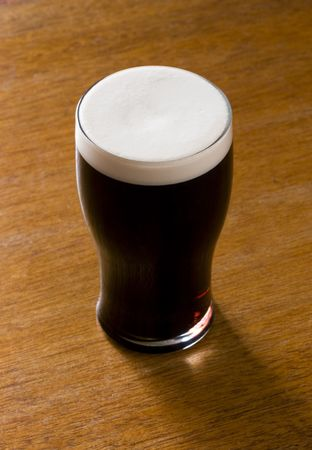 paddys: A pint of stout on a wooden bar table. Stock Photo