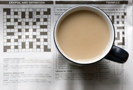 clues: A full cup of tea sitting on top of a semi solved crossword puzzle. Stock Photo