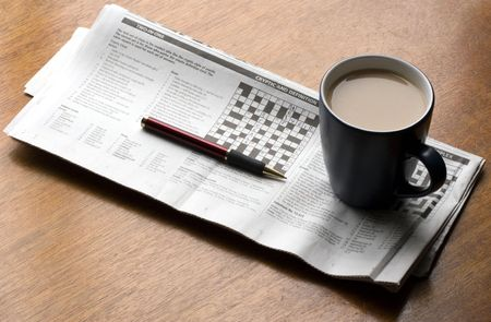 A cup of tea placed on a crossword puzzle with pen placed on a wooden table. photo