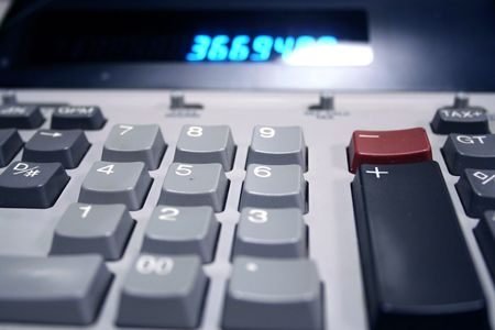 adding: Adding machine showing the keyboard with a blurred number