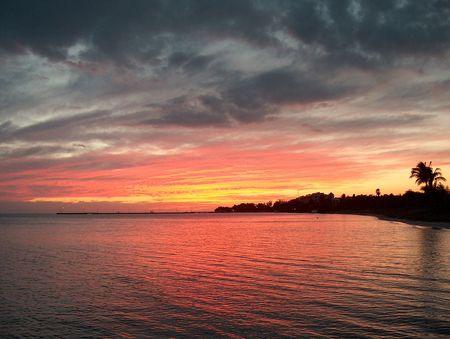 clave sol: Una puesta del sol imponente con las nubes de la tormenta que ruedan adentro en una playa en el oeste dominante Foto de archivo