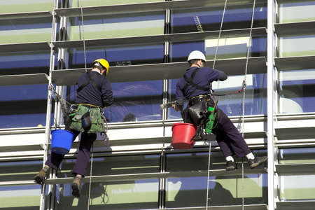 accidente laboral: Trabajadores Abseiling Un Edificio Corporativo
