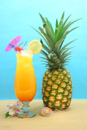 Pineapple and Drink on Sand With Blue Background