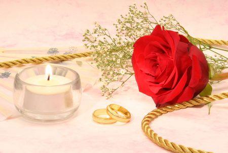 wedding bands: Rose con bandas de bodas de oro y velas de color rosa sobre fondo  Foto de archivo