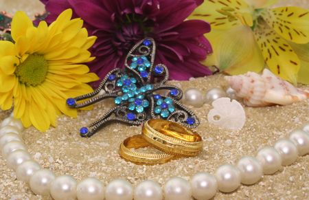 Sea Shells With Flowers and Wedding Rings on Sand