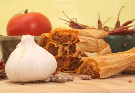 Garlic with Tamales and Beans on Yellow Background Stock Photo