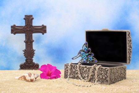 broach: Jewelry Box on sand With Cross and Blue Sky Background