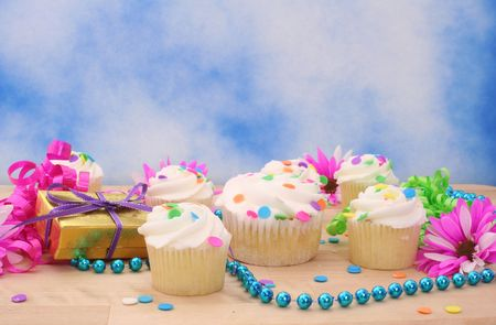 Flowers and Cupcakes with Gift on Blue Sky Background Stock Photo
