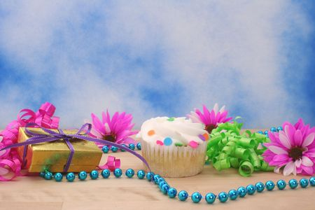 Flowers and Cupcake with Gift on Blue Sky Background photo