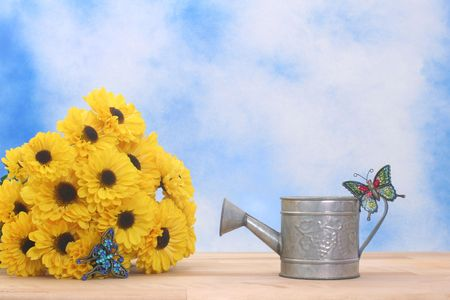 Metal Watering Can on Blue Sky Background With Betterflies and Flowers
