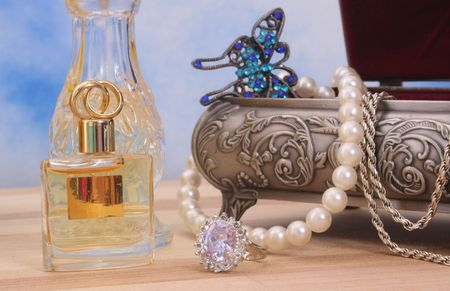 Jewelry and Perfume on Wood With Blue Sky Background photo