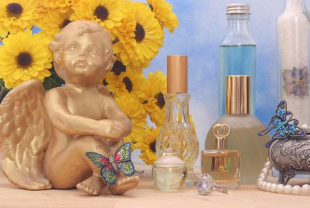 Jewelry and Perfume with Flowers and Angel on Blue and White Textured Background, Close-up photo