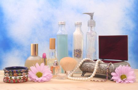Jewelry Box With Cosmetics, Flowers and Perfume on Blue Textured Background photo