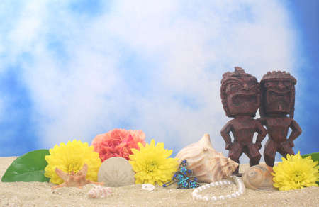 Tiki Statue on Sand With Flowers and Sea Shells Stock Photo