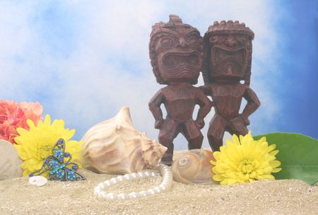 Tiki Statue With Flowers and Sea Shells on Blue Sky Background