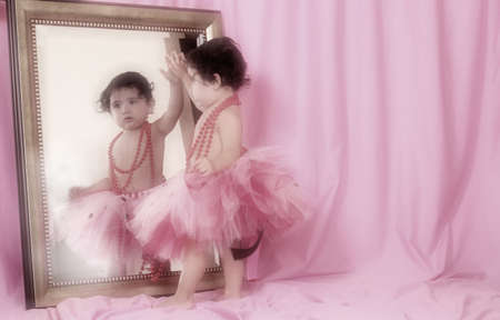mirror: Little Girl in Tutu Looking into Mirror with Pink Background