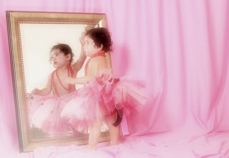Little Girl in Tutu Looking into Mirror with Pink Background