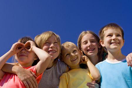 Smiling children on blue sky photo