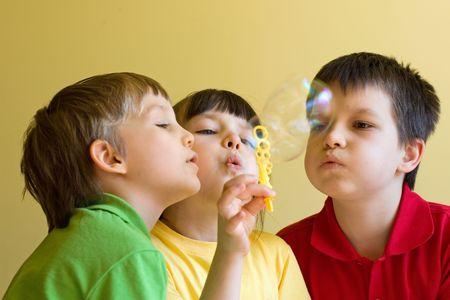 Three Children Blow Bubbles photo