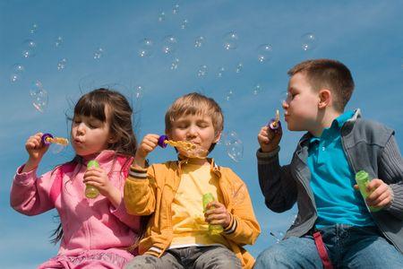 Los ni�os soplando burbujas  Foto de archivo