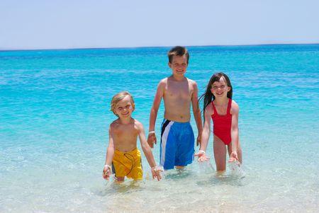 Three Children Wading in Ocean photo