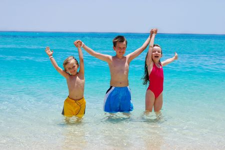 Three Children Wading in Ocean photo