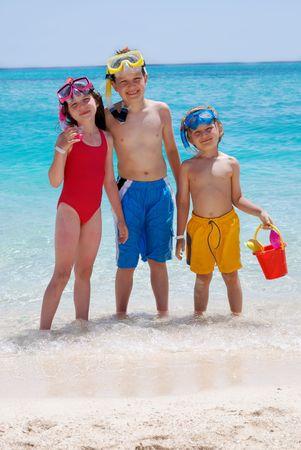 trois enfants: Trois enfants Pataugeant dans loc�an Banque d'images