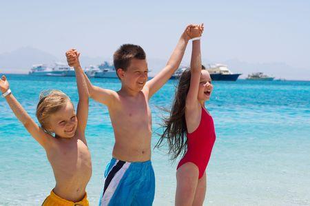 trois enfants: Trois enfants en rivi�re � gu� dans l'oc�an