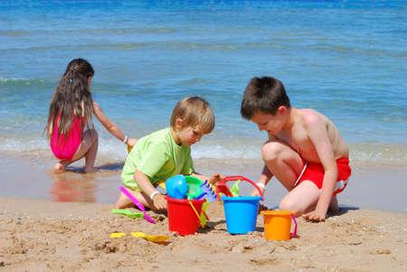 ni�as jugando: ni�os que juegan en la playa