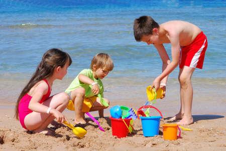 hermanos jugando: ni�os que juegan en la playa
