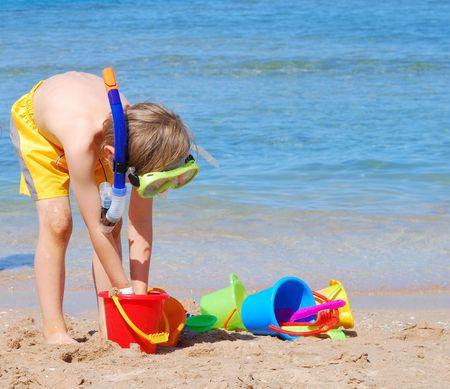 Boy with toys on the beach