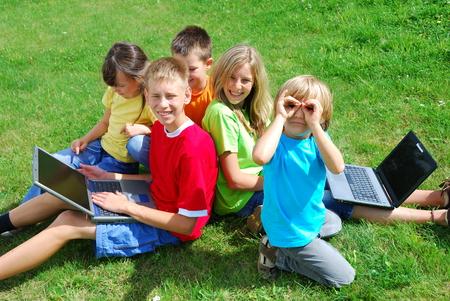 Los niños usando computadoras portátiles fuera  Foto de archivo - 1598914