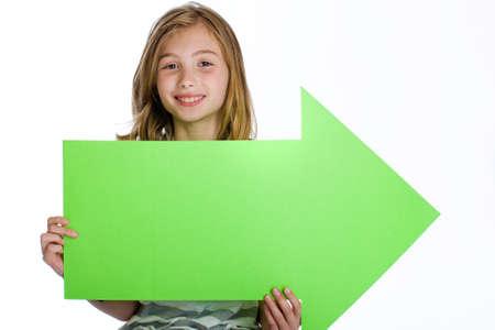 ni�os sosteniendo un cartel: ni�o que tiene se�al de flecha en blanco Foto de archivo