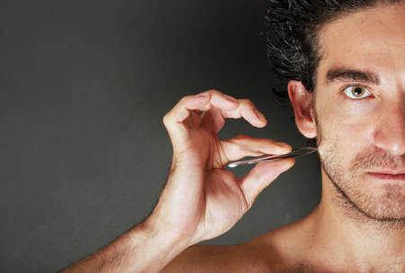 pinzas: Hombre tirando de su barba con pinzas  Foto de archivo